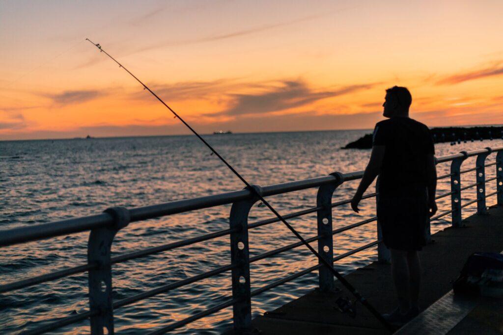 man on a sarasota fishing pier at sunset